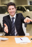 Man giving a customer keys while reaching for handshake Royalty Free Stock Photos