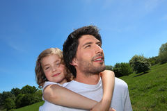 Man giving daughter piggyback royalty free stock images