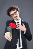Man giving fabric rose. Boy with glasses is donating a fabric red rose Stock Photography