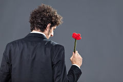 Man giving fabric rose. Boy is donating a fabric red rose while facing on his back Royalty Free Stock Photo