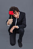 Man giving fabric rose. Boy with jacket is donating a fabric red rose Stock Photo