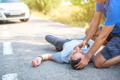 Man giving first aid in car accident stock image