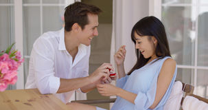 Man giving flattered woman a ring at table Royalty Free Stock Photography