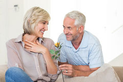 Man giving flower to a smiling woman sitting on couch Royalty Free Stock Image