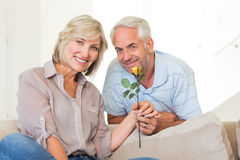 Man giving flower to a smiling woman sitting on couch Royalty Free Stock Images
