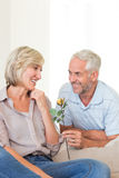 Man giving flower to a smiling woman sitting on couch Royalty Free Stock Photography
