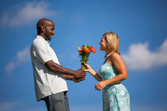 Man Giving Flowers. Handsome black men giving beautiful caucasian women flowers on a sunny summer afternoon Stock Image