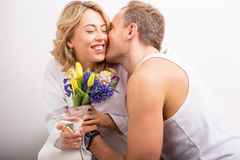 Man giving flowers and kissing girlfriend on her cheek Royalty Free Stock Image