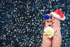 Man is giving flowers to a woman. Face painted on the fingers. Man is giving flowers to a woman Royalty Free Stock Photo