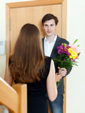 Man giving flowers to woman. Smiling men giving flowers to women at home door stock photos