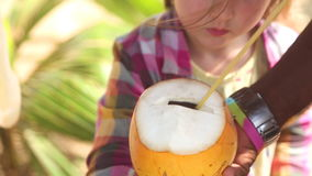 Man giving fresh coconut drink to a little girl stock video