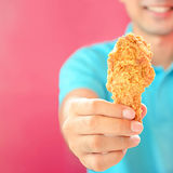 A man giving fried chicken leg or drumstick Stock Photography
