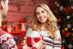 Man giving a gift to his girlfriend, romantic surprise. For Christmas. Young blond women receiving a little red gift box Royalty Free Stock Photography
