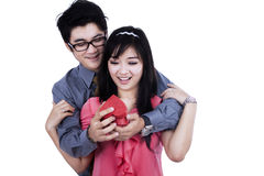A man giving a gift to his girlfriend. Young men giving a gift to his girlfriend on valentine's day Stock Photography