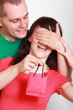 Man giving a gift to surprised smiling woman Royalty Free Stock Images