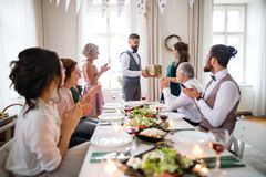 A man giving gift to a young surprised woman on a family birthday party. stock image