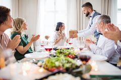 A man giving gift to a young surprised woman on a family birthday party. stock photography