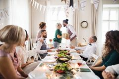 A man giving gift to a young surprised woman on a family birthday party. royalty free stock photo