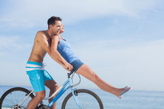 Man giving girlfriend a lift on his crossbar Stock Image