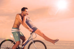 Man giving girlfriend a lift on his crossbar Stock Photo