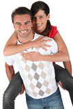 Man giving girlfriend piggyback Stock Photo