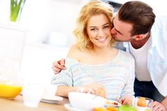 Man giving good morning kiss to his wife Stock Images