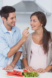 Man giving a grape to his pregnant partner Stock Images