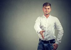 Man giving hand for shaking. Confident young man outstretching hand for handshake when greeting partner on gray background stock image