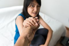 Man giving hand to depressed asian woman,Mental health care concept. Man giving hand to depressed asian woman on bedroom,Mental health care concept stock image