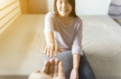Man giving hand to depressed woman,Such as making a fresh start and loving yourself,Mental health care concept. Man giving hands to depressed woman,Such as stock photo