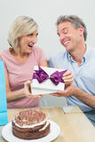 Man giving a happy woman a birthday gift beside cake Royalty Free Stock Images