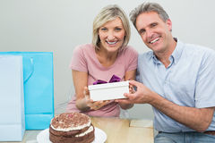 Man giving a happy woman a birthday gift beside cake Stock Photo