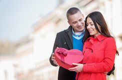 Man giving a heart-shaped present to his girlfriend stock photography
