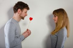 Man giving heart to his girl. Romance symbolism valentines concept. Man giving heart to his girl. Young male proffesing love to woman, by giving her heart Royalty Free Stock Image