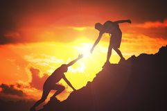 Man is giving helping hand. Silhouettes of people climbing on mountain at sunset.  stock photo