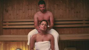 Man giving his girlfriend a neck massage in the sauna. At the hotel spa stock video