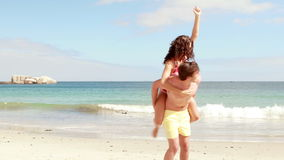 Man giving his girlfriend a piggy back at the beach. In 4k format man giving his girlfriend a piggy back at the beach stock footage