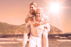 Man giving his laughing wife a piggy back at the beach Stock Images