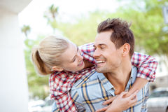 Man giving his pretty blonde girlfriend a piggy back Stock Image