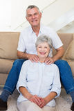 Man giving his relaxed senior wife a shoulder rub smiling at camera Stock Photos