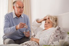 Man giving his sick wife pills Royalty Free Stock Photos