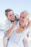 Man giving his smiling wife a piggy back at the beach Stock Image