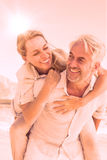 Man giving his smiling wife a piggy back at the beach Stock Photography