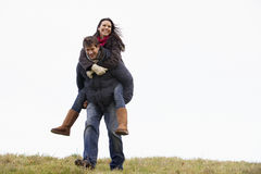 Man Giving His Wife Piggy Back Ride Stock Photography