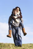 Man Giving His Wife A Piggy Back Ride Stock Photography