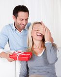 Man giving his wife a surprise gift. At home Royalty Free Stock Photography