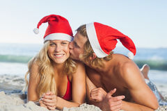 Man giving kiss to partner wearing christmas hats Stock Images