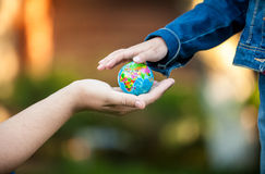Man giving little girl globe on hand. Closeup shot of men giving little girl globe on hand Royalty Free Stock Images