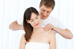 Man giving massage to his wife. At home Stock Photos
