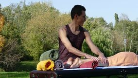 Man giving massage to young brunette outdoors stock video footage